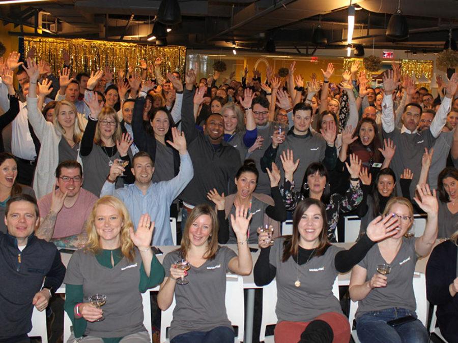 group of people waving at a camera
