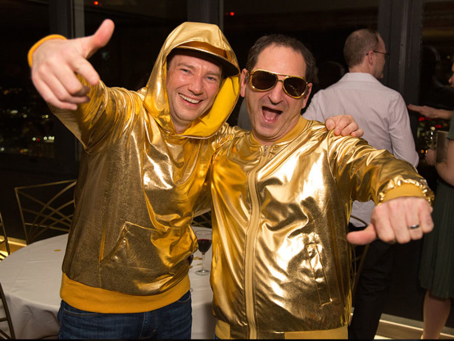 People posing for a photo wearing gold jackets