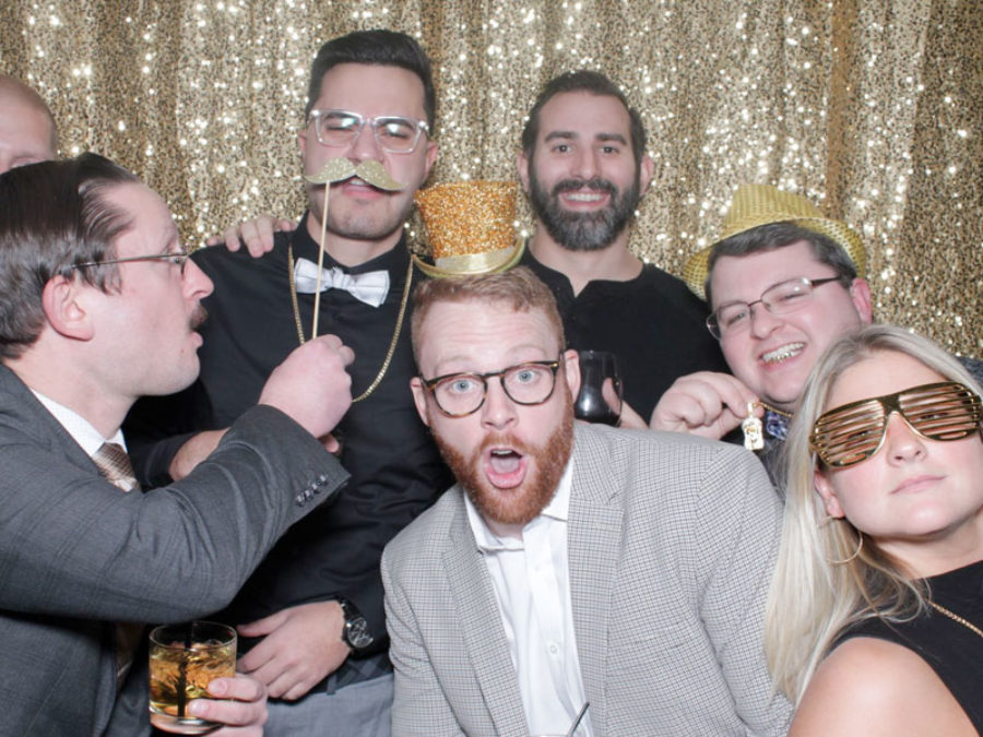 People dressed up in a photo booth playing with props