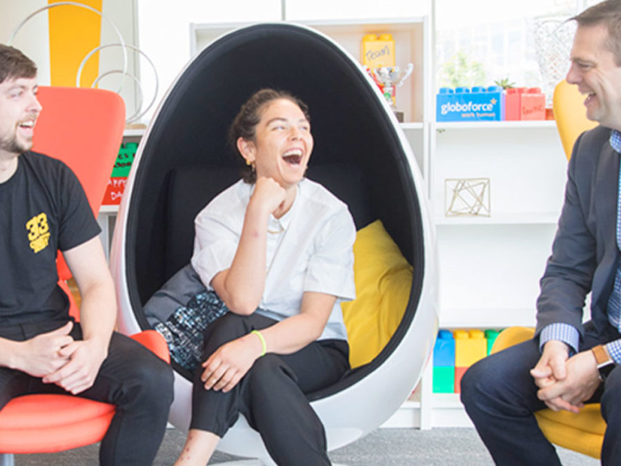 People laughing and sitting in the egg chairs