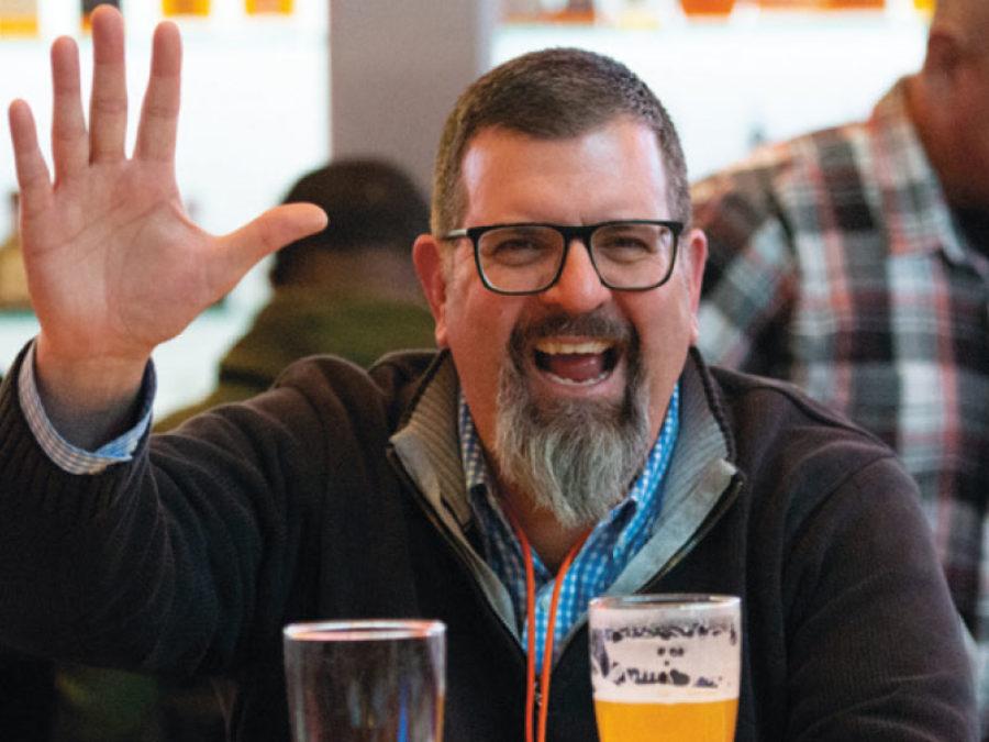 Man waving at camera with a drink